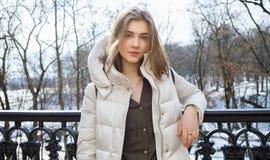 Schöne junge Blondine, die auf dem Frühlingsstadtpark in der warmen Kleidung stehen Kaltes Jahreszeitlebensstil-Frischekonzept Stockfotografie