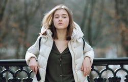 Schöne junge Blondine, die auf dem Frühlingsstadtpark in der warmen Kleidung stehen Kaltes Jahreszeitlebensstil-Frischekonzept Lizenzfreie Stockfotos