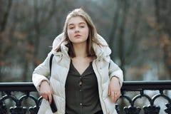 Schöne junge Blondine, die auf dem Frühlingsstadtpark in der warmen Kleidung stehen Kaltes Jahreszeitlebensstil-Frischekonzept Stockbilder