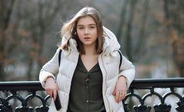 Schöne junge Blondine, die auf dem Frühlingsstadtpark in der warmen Kleidung stehen Kaltes Jahreszeitlebensstil-Frischekonzept Lizenzfreies Stockfoto