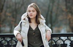 Schöne junge Blondine, die auf dem Frühlingsstadtpark in der warmen Kleidung stehen Kaltes Jahreszeitlebensstil-Frischekonzept Lizenzfreie Stockbilder