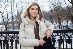 Schöne junge Blondine, die auf dem Frühlingsstadtpark in der warmen Kleidung stehen Kaltes Jahreszeitlebensstil-Frischekonzept Stockfoto
