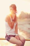 Schöne junge Blondine, die auf dem Strand sitzen Tragendes weißes T-Shirt Wind brennt in ihr langes blondes Haar durch In Lizenzfreies Stockbild