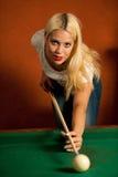 Schöne junge Blondine, die Billard in einer Stange spielen Stockbild