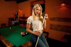 Schöne junge Blondine, die Billard in einer Stange spielen Lizenzfreies Stockfoto