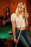 Schöne junge Blondine, die Billard in einer Stange spielen Stockfotografie