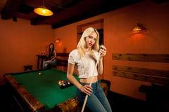 Schöne junge Blondine, die Billard in einer Stange spielen Lizenzfreies Stockbild