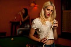 Schöne junge Blondine, die Billard in einer Stange spielen Lizenzfreie Stockbilder