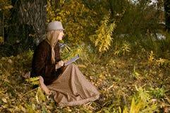 Schöne junge Blondine, die draußen in den letzten Sonnenstrahlen an der Herbstsonnenuntergangfarbe eine Skizze im Notizblock sitz Lizenzfreie Stockfotografie