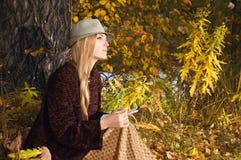 Schöne junge Blondine, die draußen in den letzten Sonnenstrahlen an der Herbstsonnenuntergangfarbe eine Skizze im Notizblock sitz Stockbilder