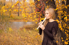 Schöne junge Blondine, die Flötenrecorder im Herbstwald spielen Stockfoto