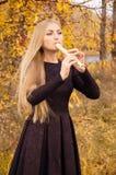 Schöne junge Blondine, die Flötenrecorder im Herbstwald spielen Stockfotos