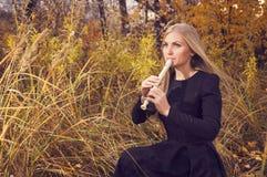 Schöne junge Blondine, die Flötenrecorder im Herbstwald spielen Stockbild