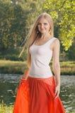 Schöne junge Blondine, die im Wald nahe Riverbank aufwerfen Lizenzfreie Stockbilder