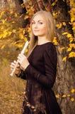 Schöne junge Blondine, die mit Flötenrecorder im Herbstwald aufwerfen Lizenzfreie Stockfotos