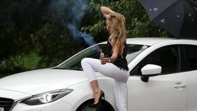 Schöne junge Blondine, die nahe weißem Auto stehen Herrliche Mädchenhaltungen mit Rauche Langsame Bewegung stock footage