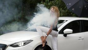 Schöne junge Blondine, die nahe weißem Auto stehen Herrliche Mädchenhaltungen mit Rauche Langsame Bewegung stock video