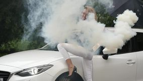 Schöne junge Blondine, die nahe weißem Auto stehen Herrliche Mädchenhaltungen mit Rauche Langsame Bewegung stock video footage