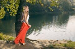 Schöne junge Blondine, die unter dem Baum auf Riverbank aufwerfen Lizenzfreie Stockbilder