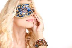 Schöne junge Blondine in einer mysteriösen venetianischen Maske. Stockfoto