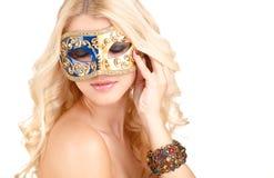 Schöne junge Blondine in einer mysteriösen venetianischen Maske. Stockbild