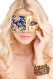 Schöne junge Blondine in einer mysteriösen venetianischen Maske. Stockfotos