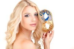 Schöne junge Blondine in einer mysteriösen venetianischen Maske. Lizenzfreie Stockfotografie