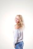Schöne junge Blondine in einer Weste und in den Jeans auf einem weißen Hintergrund Stockfotos