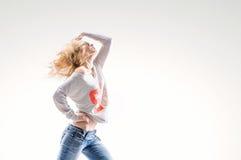 Schöne junge Blondine in einer Weste und in den Jeans auf weißem Hintergrund mit Energietanz ziehen um Stockfotografie
