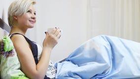 Schöne junge Blondine erhalten einen Tasse Kaffee im Bett stock video footage