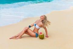 Schöne junge Blondine im Bikini liegt auf ein tropischen Strand wi stockfotografie