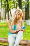 Schöne junge Blondine im blauen T-Shirt sitzen auf Bank und w stockfotografie