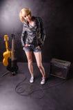 Schöne junge Blondine kleidete in der schwarzen Lederjacke mit E-Gitarre auf einem schwarzen Hintergrund an Stockfotos