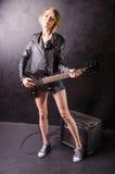 Schöne junge Blondine kleidete in der schwarzen Lederjacke mit E-Gitarre auf einem schwarzen Hintergrund an Stockfoto