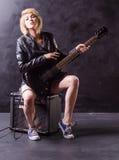 Schöne junge Blondine kleidete in der schwarzen Lederjacke mit E-Gitarre auf einem schwarzen Hintergrund an Lizenzfreie Stockbilder