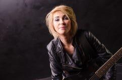 Schöne junge Blondine kleidete in der schwarzen Lederjacke mit E-Gitarre auf einem schwarzen Hintergrund an Lizenzfreie Stockfotografie