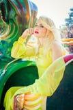Schöne junge Blondine am langen elegantes Kleidermodeporträt-Sommertag im Freien im StadtVergnügungspark stockfotografie