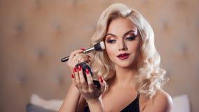 Schöne junge Blondine macht ein helles Feiertagsmake-up Bezauberndes Make-up lizenzfreies stockbild