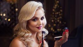 Schöne junge Blondine macht ein helles Feiertagsmake-up Bezauberndes Make-up Eine attraktive junge Frau benutzt Pulver lizenzfreie stockfotos