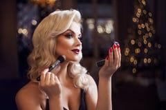 Schöne junge Blondine macht ein helles Feiertagsmake-up Bezauberndes Make-up Eine attraktive junge Frau benutzt Pulver lizenzfreies stockfoto