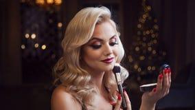 Schöne junge Blondine macht ein helles Feiertagsmake-up Bezauberndes Make-up Eine attraktive junge Frau benutzt Pulver stockfotos