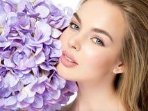 Schöne junge Blondine mit Blumen nähern sich Gesicht Stockfoto