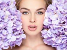 Schöne junge Blondine mit Blumen nähern sich Gesicht Lizenzfreie Stockbilder