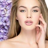 Schöne junge Blondine mit Blumen nähern sich Gesicht stockfotografie