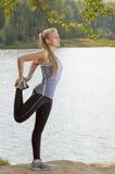 Schöne junge Blondine mit dem athletischen Körper, der Übung draußen ausdehnend tut Lizenzfreie Stockbilder