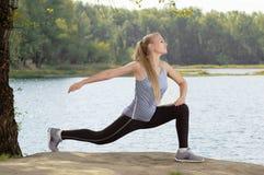 Schöne junge Blondine mit dem athletischen Körper, der Übung draußen ausdehnend tut Lizenzfreie Stockfotografie