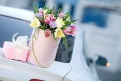 Schöne junge Blondine mit dem gewellten Haar draußen mit einem großen Blumenstrauß von Blumen auf einer hellen Straße in der lizenzfreie stockbilder