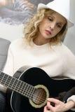 Schöne junge Blondine mit dem Hut, der das akustische guita spielt Lizenzfreie Stockfotos