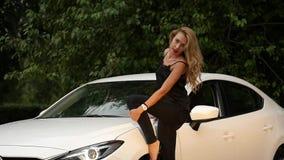 Schöne junge Blondine mit dem langen Haar, das nahe weißem Auto steht stock video footage
