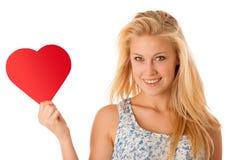 Schöne junge Blondine mit den blauen Augen, die rotes Hirschverbot halten Stockbild